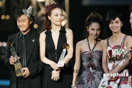 """一月十九日晚,""""第三十届十大中文金曲颁奖典礼""""在香港体育馆举行,陈奕迅、容祖儿和Twins(从左至右)分获第三十届十大中文金曲全年最高销量男歌手、女歌手、组合奖。十大中文金曲颁奖典礼由香港电台主办,是大中华地区最重要的流行音乐颁奖项目之一,亦是历史最悠久的华语流行音乐颁奖盛会。中新社发武仲林 摄"""