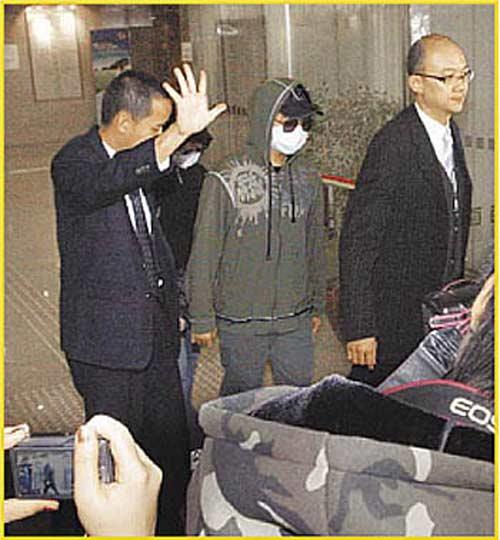 涉案男子史可隽(中)昨戴帽子、墨镜、口罩,在律师陪同下出庭