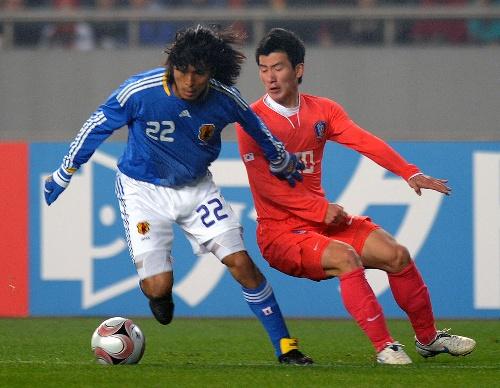 ...2月23日,日本队球员中泽佑二(左)与韩国队球员拼抢.当日,在重...