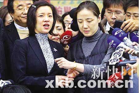 沈嵘(右)与璩美凤紧握双手,在媒体的包围下离开监狱。