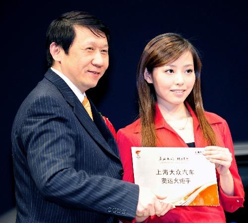 歌手张靓颖(右)接受火炬手证书