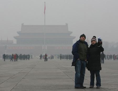 """资料图片:12月27日,游客在北京天安门广场游览。当日,雾霾笼罩京城。这是北京连续出现雾霾天。24日开始缠绕北京的雾气在25日下午演变成了""""霾"""",空气变得干燥,空气质量随之严重下滑。(新华社记者"""