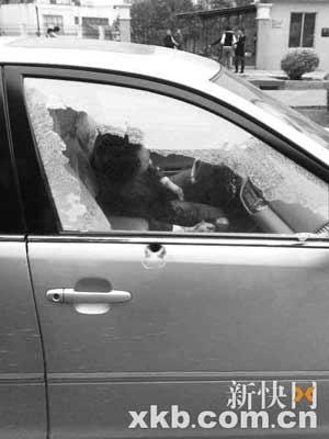 ■白色轿车驾驶室右侧玻璃粉碎,黑衣男子身中数枪昏死过去。读者供图