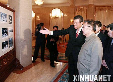 中国驻朝鲜大使刘晓明(前左)陪同朝鲜最高领导人金正日(前右)观看使馆展出的纪念周恩来诞辰110周年的图片展览。