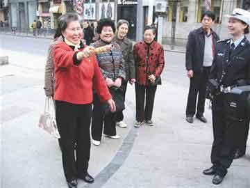 邱益英(左一)比划当年的指挥手势记者吴昌华摄