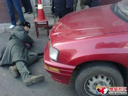 照片中一个保安躺下横在车辆前阻挡司机出门