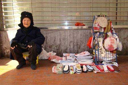 资料图:94岁老太太,街上卖自制鞋垫谋生。