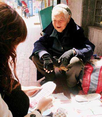 资料图:老太太正在卖鞋垫。