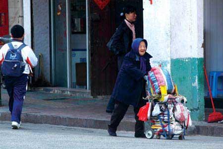 资料图:老太太正在推着卖鞋垫的车子。