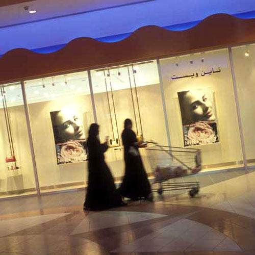 阿曼妇女经过商场橱窗