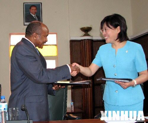 达累斯萨拉姆市长亚当·金比萨(左)与北京奥组委火炬接力中心主任张明交换签署完毕的协议书