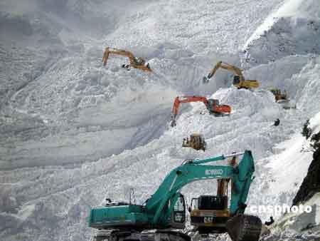 事故现场目前大雾弥漫,不时有零星雪崩,严重影响了救援工作的开展。 中新社发 皮峰 摄