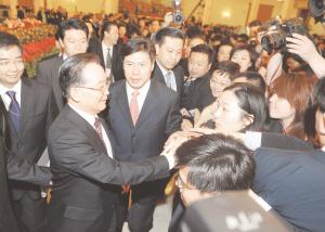 图为温家宝总理和参加中外记者招待会的本报记者周婷亲切握手。文/周婷 新华社图片
