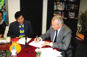 斯达夫诺斯·杜维斯(右)为中国读者题字:祝好运,我爱你们!(左上图) 特派记者 王敏 摄