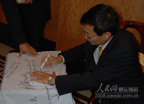张明大使在奥运旗上签名留念