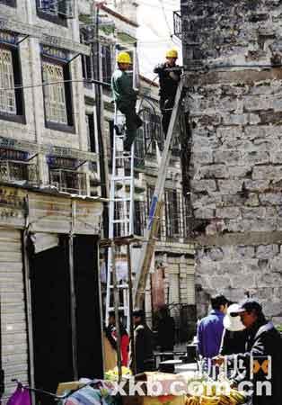 ■工作人员在修复受损的房屋。
