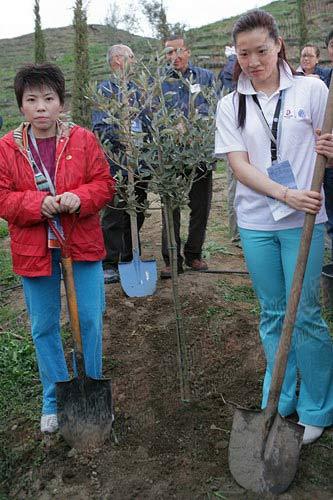 图文:罗雪娟、邓亚萍在顾拜旦墓植树 邓亚萍和罗雪娟手举铁锹