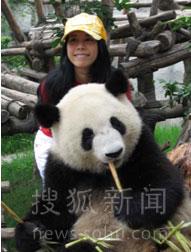 莫小姐头戴黄色棒球帽身着一件胸口印有可爱熊猫图案的红色休闲T恤与熊猫合影
