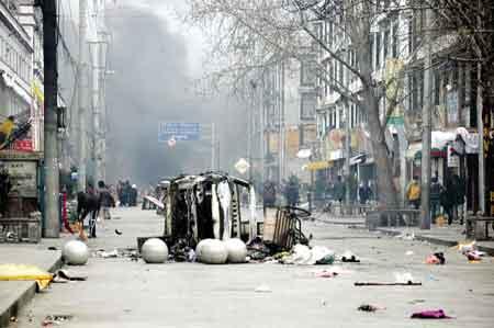 """在""""3·14""""打砸抢烧暴力事件中,暴徒们见人就砍、进店就抢、见车就烧。图为被暴徒们洗劫、破坏的夏萨苏东路上浓烟滚滚、满目疮痍。西藏日报记者"""
