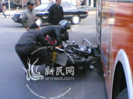 摩托车被卡在公交车下 新民网记者 潘佳摄