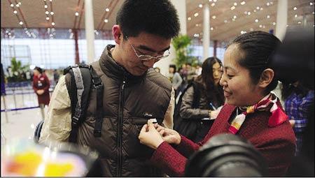 """今天上午,乘坐""""国航T3早高峰首航班""""的乘客小喻被戴上""""标牌"""" 摄/记者林晖"""
