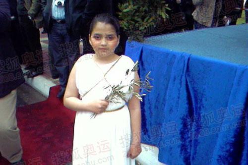 年幼的小祭司手拿橄榄枝迎接圣火