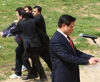 闹事者被希腊警察制服,并被带离现场,北京奥组委主席刘淇继续沉稳庄严地发表讲话。图片来源:国际在线