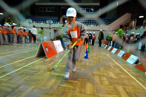一名参加奥运社区行的小朋友在练习曲棍球