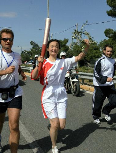 中国火炬手乔力(中)在马拉松市手持圣火传递