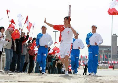 3月31日,刘翔手持火炬跑过金水桥。当日,北京2008年奥运会圣火欢迎仪式暨火炬接力启动仪式在天安门广场举行。 新华社记者鞠鹏摄