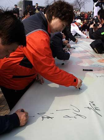 奥运冠军孙福明等和阳泉群众一起在心向北京奥运的百米长卷上签名