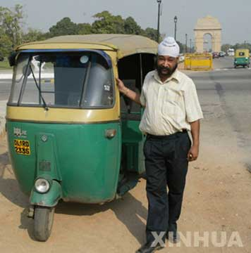 """新德里印度门前的""""摩的""""。这种摩托车乘费便宜、轻巧灵活,使用清洁燃料也减轻了尾气对大气的污染,很受当地居民的欢迎,是新德里最常见的出租车"""