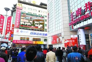 昨天,人们在北京王府井大街观看奥运会圣火抵达北京的电视直播。 新华社记者 王庆钦摄