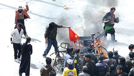 3月14日, 在拉萨市,一名不法分子在焚烧中国国旗,另一名不法分子手持长刀