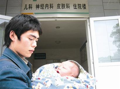 邓秋洪抱着孩子心急如焚。