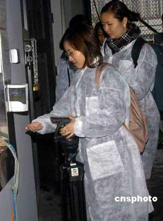 四月一日,香港沙田奥运马术比赛场地工程大致完成,并首次开放予传媒采访。图为进出马房的人士都要穿上保护衣,并要用洗手液消毒。中新社发谭达明 摄