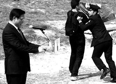 """在奥运圣火点火仪式上,一名""""无疆界记者组织""""成员在北京奥组委主席刘淇发表讲话时打开横幅""""闹场"""""""