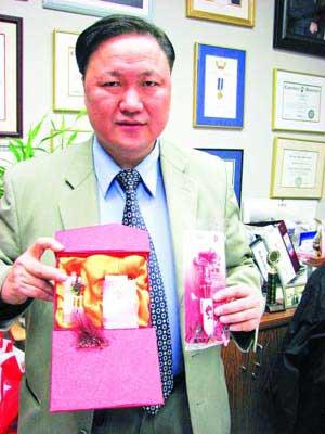 担任今年北京奥运会志愿者的陆炳雄﹐介绍有关2008北京奥运的各类纪念物品。(加拿大《明报》/孔伟民 摄)