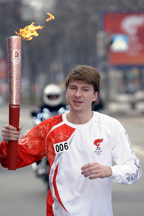 冬奥会冠军亚古金手持火炬在圣彼得堡传递