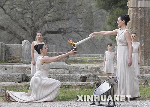 3月24日,北京奥运会圣火取火仪式在希腊奥林匹亚举行。图为扮演最高女祭司的玛利亚?娜芙普利都(前右)点燃火种罐。 新华社记者戚恒摄