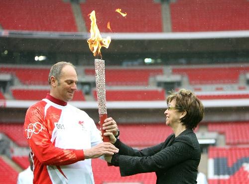 4月6日,在圣火传递起点――温布利体育场,大伦敦市副市长尼基·盖夫隆(右)将火炬交给第一棒火炬手史蒂夫·雷德克雷夫。当日,北京奥运会圣火传递活动在英国伦敦举行,这是北京奥运会圣火境外传递的第四站。 新华社记者谢秀栋摄