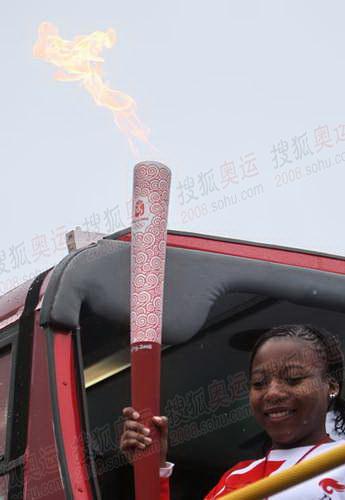 图文:第二棒火炬手在双层巴士上展示圣火