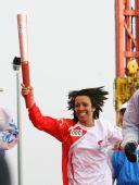 图文:奥运圣火在伦敦传递 火炬手高举火炬奔跑