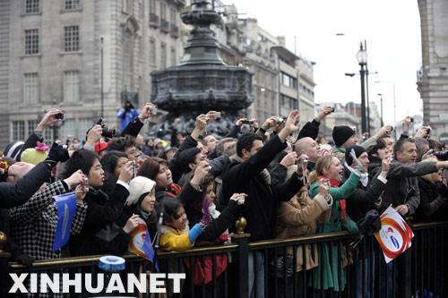 """4月6日,观众在伦敦观看奥运圣火传递。 当日,英国伦敦警方逮捕了极少数企图干扰破坏奥运圣火传递的""""藏独""""分子。 新华社记者 戚恒 摄"""