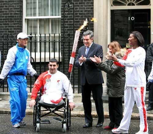 在首相府前,英国首相布朗(左三)、英国奥运事务大臣特莎·乔维尔(左四)和第34棒火炬手、英国田径名将丹尼斯·刘易斯(右一)欢送第35棒火炬手阿里·贾瓦德