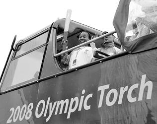 昨天,火炬手康妮手持火炬站在伦敦巴士上传递。