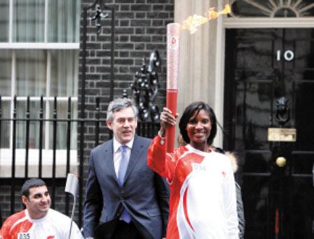 4月6日,在首相府前,英国田径名将刘易斯(右)手持火炬在首相布朗(中)旁边展示。新华社发