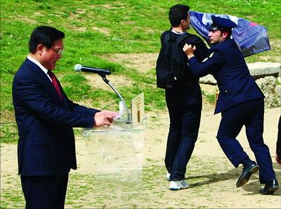 """在北京奥组委主席刘淇发表讲话时,一名""""记者无疆界组织""""成员打开横幅""""闹场""""。"""