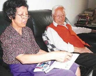 王俊嵘(右)与徐月美(左)夫妇保存着新疆女大学生唐红寄来的信,看着她的成绩单,两人十分欣慰。台湾《联合报》记者翁祯霞摄