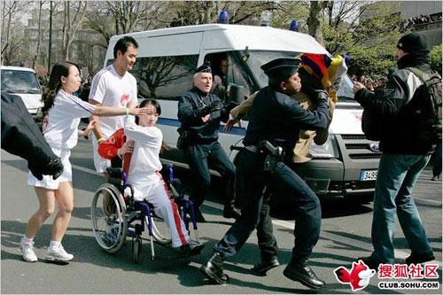 阳光美女金晶用残缺的身体保护奥运火炬  推轮椅那位是盲人 图片由搜狐网友提供